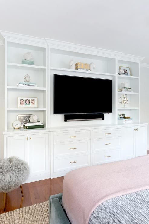 Wall Units Bedroom Furniture A Blue Velvet Upholstered Bed Faces A Built In Media Center